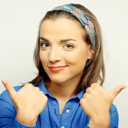 young girl gives thumb up with two hands