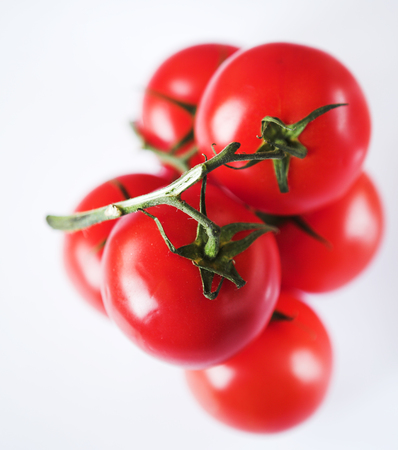 tomatoes on a green twig on white background