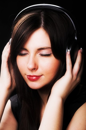 A beautiful woman listening to music intensely.
