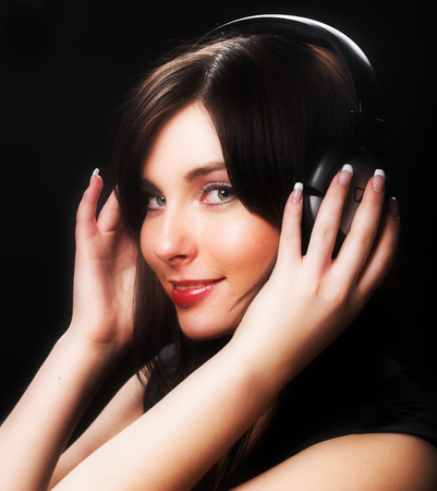 A beautiful woman smiling and listening to music.