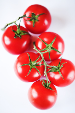 Red tomatoes on a green twig on white background