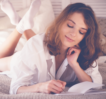 drawing room: lifestyle soft image of pretty young woman sitting on her cozy Stock Photo