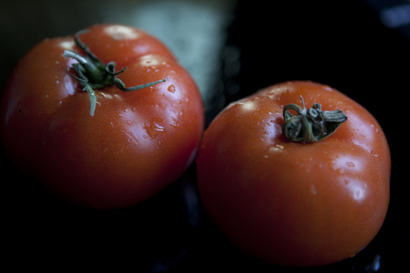 drop water: Two fresh red tomatoes on dark background Stock Photo