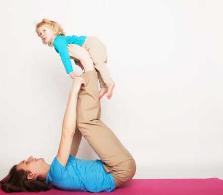 sport  and people concept: father and her son doing yoga exercise on studio white background.