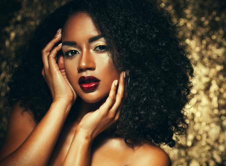 jonge elegante Afrikaanse Amerikaanse vrouw met afrohaar. Glamour make-up. Gouden achtergrond.