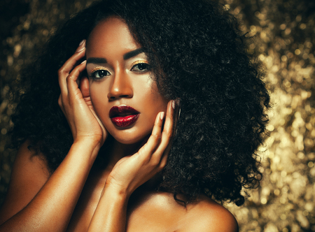 young elegant african american woman with afro hair. Glamour makeup. Golden Background.