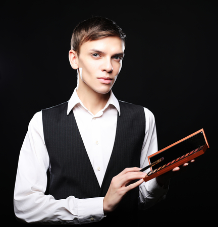 Male make-up artist  staying on dark  background, holding profes