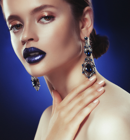 Fashion portrait of young beautiful woman with jewelry. Perfect make-up. Blue lips. Stock Photo