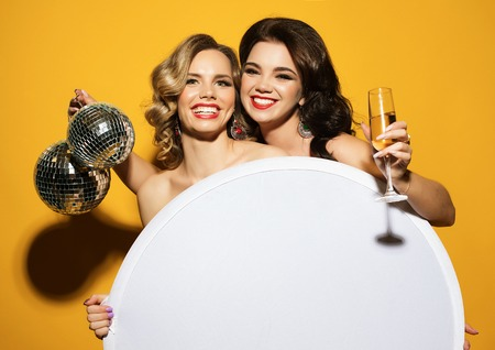 beautiful young women with wine glasses and disco ball.