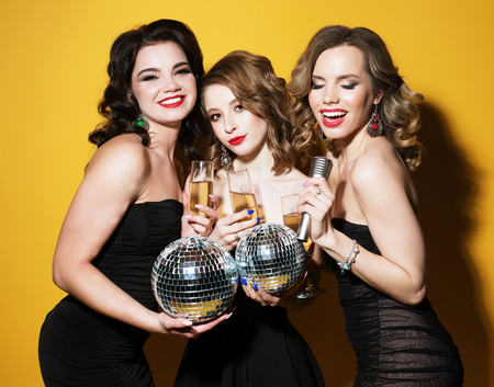 charming young women with disco balls  drinking champagne