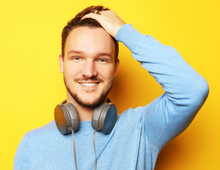 smart young smiling man standing against yellow background