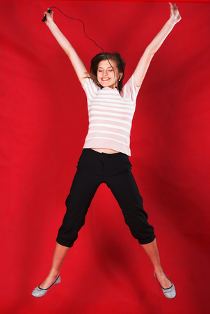 attractive woman jumping of joy over red Stock Photo