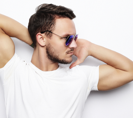 young man in smart wear, wearing fashion sunglasses against whit Stock Photo