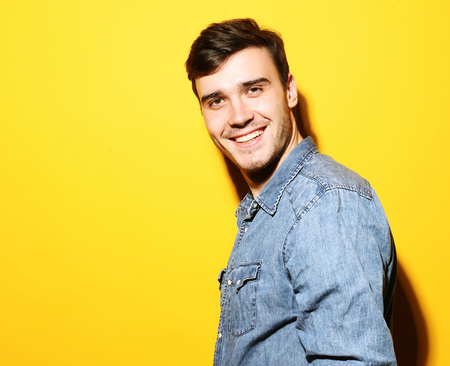 Portrait of young smiling man standing against yellow background