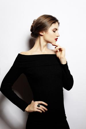 Belle jeune femme vêtue d'une robe noire posant sur le dos blanc Banque d'images - 96966207