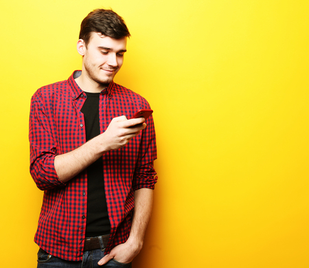 Giovane felice che parla sul telefono cellulare sopra fondo giallo