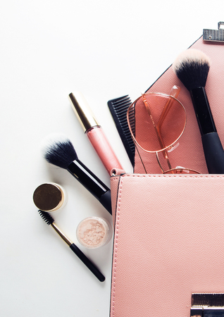 Flat lay of female fashion accessories and pink  handbag on whit