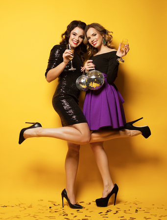 Two beautiful elegant women celebrate party and drinking champagne.