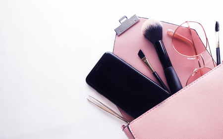 Flat lay of pink leather woman bag open out with cosmetics