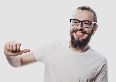 Attractive young man in  eyeglasses pointing to his blank white tshirt with index finger, showing empty space for your advertising text , isolated on white background. 스톡 콘텐츠
