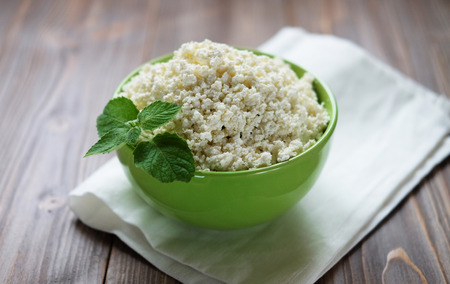 Cottage cheese with mint in a green bowl on a white napkin. Top Stock Photo