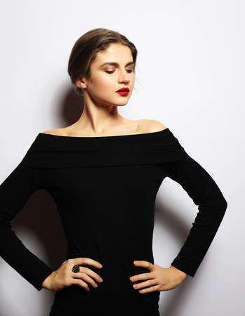 Young beautiful woman wearing black dress posing over white background 写真素材 - 97574705