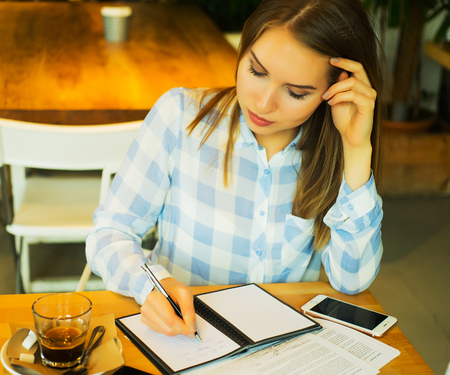 Close-up of young beautiful business woman writing in notebook Stock Photo