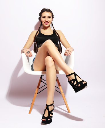Beautiful young woman  sitting on white chair Stock Photo