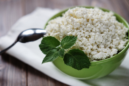 Cottage cheese with mint in a green bowl on a white napkin. Top view. Close up.
