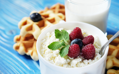 Time for breakfast. Cottage cheese with berries, waffles and milk on a wooden blue background. Close up.