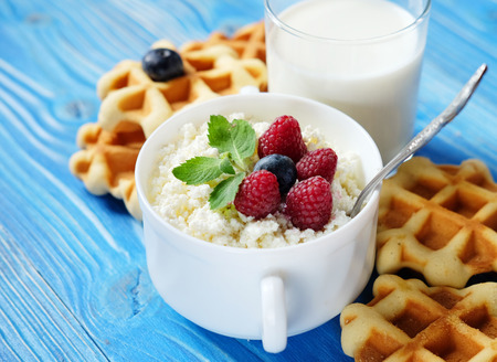Time for breakfast. Cottage cheese with berries, waffles and milk on a wooden blue background.