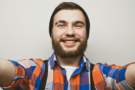I love selfie! Handsome young bearded man holding smartphone and making selfie and smiling while standing against white  background. Banco de Imagens