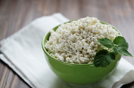 Cottage cheese with mint in a green bowl on a white napkin. Stock Photo