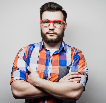 Lifestyle and people concept: Young bearded guy crossing his arms over white background Stock Photo