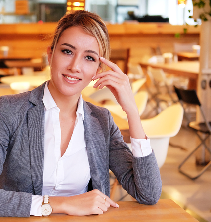 businesswoman sitting at desk and working. Smiling and looking at camera. Lifestyle, people and business concept. Close up.