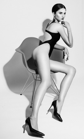 Fashion and people concept: beautiful model woman with red lips in black swimsuit sits in a chair, black and white Stock Photo