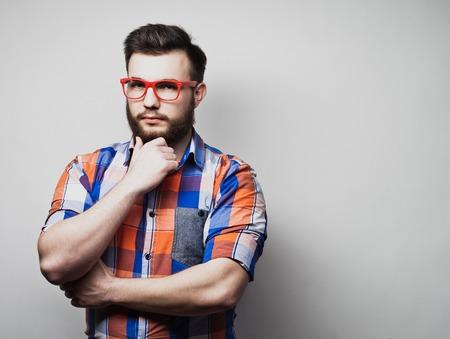 Serious bearded man wearing eyeglasses and plaid shirt.