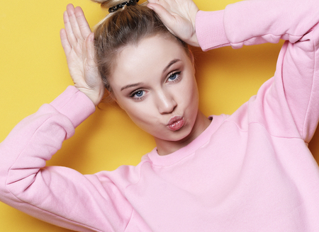 portrait of playful young pretty blond woman showing horns and making faces. Isolated on yellow background. Фото со стока