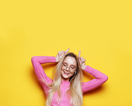 lifestyle and people concept: Look at me like Im funny. Portrait of a young beautiful girl on a yellow background with a smiling showing horns on the camera.