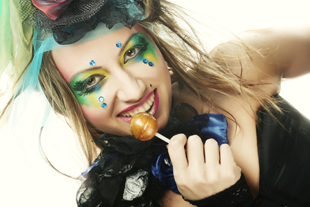 Girl with with creative make-up holds lollipop.