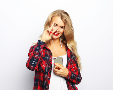 Happy young woman listening to music from smartphone 免版税图像