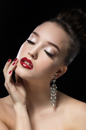Portrait of young beautiful woman with evening make up touching her face, close eyes, over black background. Stock Photo