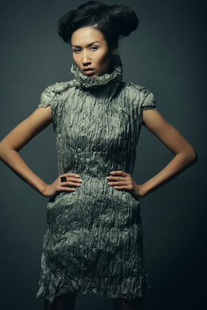 Beauty and fashion concept: young Asian fashion model in grey dress against black background