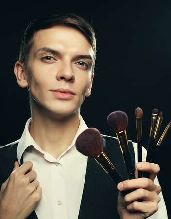 Young male make up artist posing with make-up brushes on a dark background