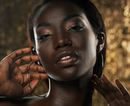 Beauty concept: Portrait of a sensual young African woman with colored make up