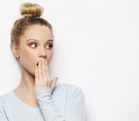 Indoor shot of stupefied shocked blonde woman keeps mouth widely opened, looks at camera, wears casual clothes, isolated over white background. Lifestyle concept.