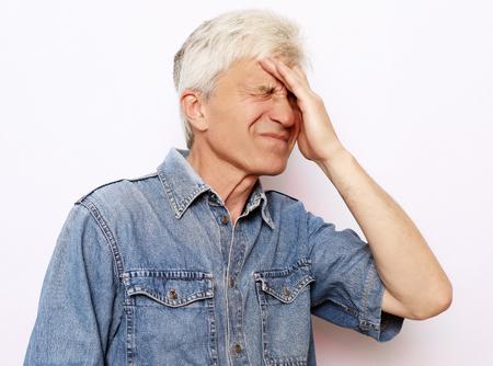 lifestyle, health  and people concept: Senior man has headache