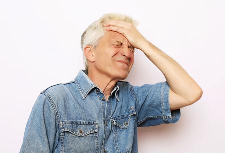 lifestyle, health and people concept: Senior man has headache, on white background Stock Photo