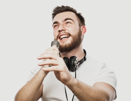 Young bearded man with headphones and microphone over white background Banco de Imagens