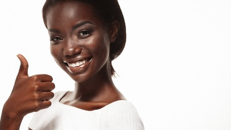 Beautiful young african  woman signaling ok, isolated over white background